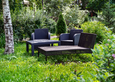 dacha: Wicker comfortable furniture made of plastic on grass in garden outside the city