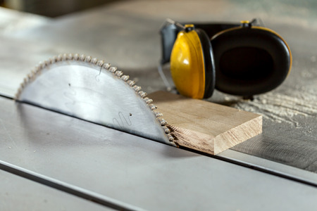 hearing protection: Circular wood saw in the carpentry workshop and hearing protection against noise at work