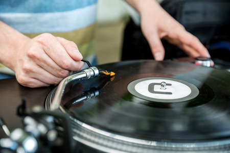 Dj playing and mixes track on Vinyl Player in club at party