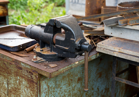 Old rusty vise on workbench in the obsolete metal rust