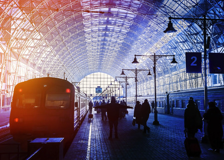 hurrying: Covered railway station with trains and silhouettes of hurrying people