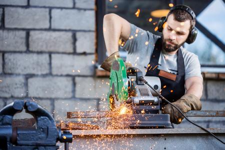 工業労働者は、多くのシャープで金属を切断は円形刃を持つ複合マイター見たの作業を火花します。 写真素材
