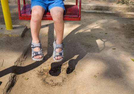 droop: Foot baby swinging on swing at playground Stock Photo