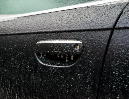 Croûte de glace recouverte d'une voiture noire pendant la pluie glacée par temps froid. Manipuler l'ouverture de la porte et les fenêtres sont recouvertes de glace après la pluie verglaçante Banque d'images - 66178537