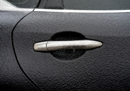 rain weather: Black car coated ice crust during the  icy rain in cold weather. Handle door opening and windows are covered with ice after freezing rain Stock Photo