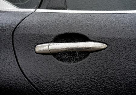 Croûte de glace recouverte d'une voiture noire pendant la pluie glacée par temps froid. Manipuler l'ouverture de la porte et les fenêtres sont recouvertes de glace après la pluie verglaçante Banque d'images - 66178508