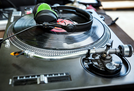 entertainment equipment: Dj mixer and vinyl player with headphones at club