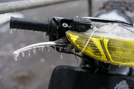 motobike: Motorcycle scooter gas and brake handle coated ice crust during the icy rain in cold weather