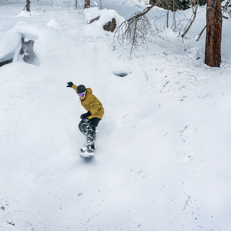 ski traces: Snowboarder jumping over the snow-covered stone on the background forest. Low angle view.
