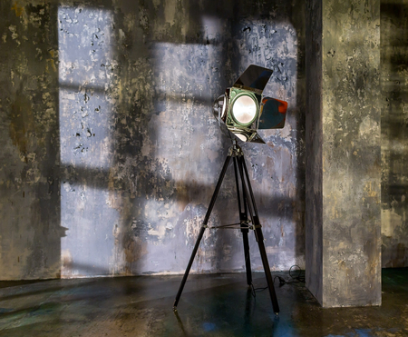 Old lamp on tripod in the background of the shabby and old walls. Large photostudio with lighting equipment Stock Photo