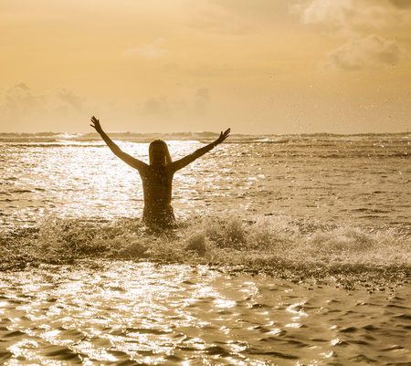 Silhouette of young young woman jumping in ocean at sunset Stock Photo