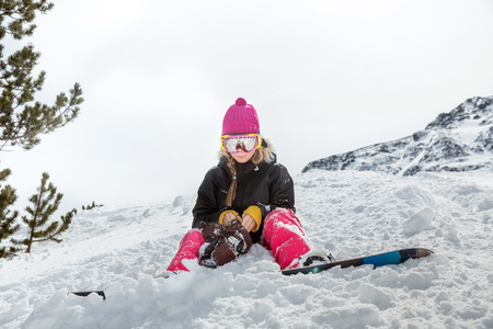 Upset young woman snowboarder after the fall sitting on the snow in mountains in winter resort