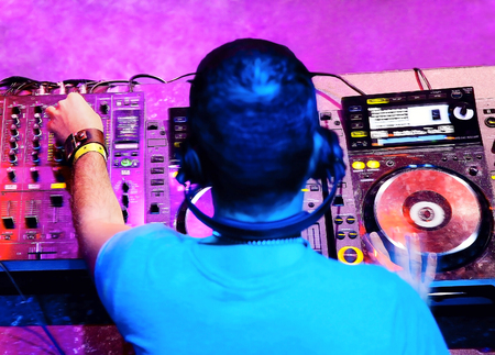 Dj in headphones mixes the track in the nightclub at party Stock Photo