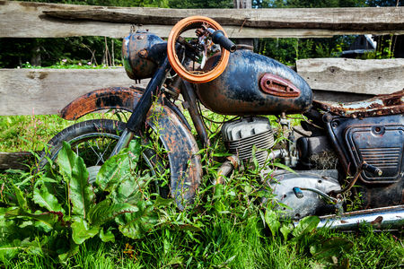 carburetor: Abandoned old Soviet motorcycle in a rural location in the village. Rusty motorbike overgrown grass near the fence