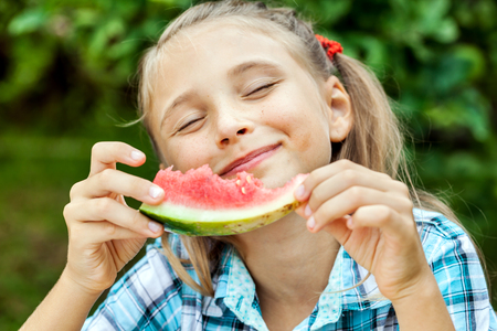 Young beautiful girl appetizing eating delicious ripe watermelon in the garden Stock Photo