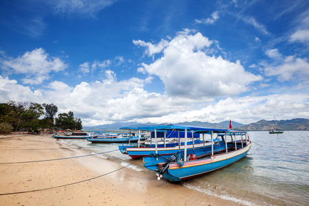 Motor boats tied to the shore to transport people or tourists from one island to another, water taxi to the Gili Islands, Indonesia.