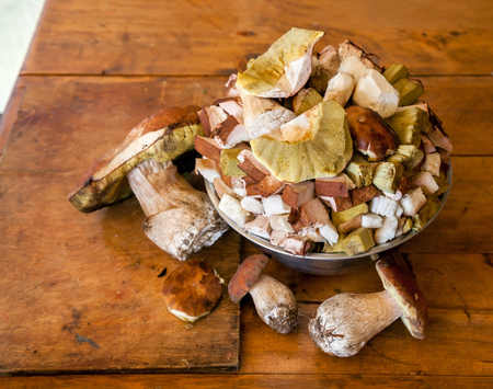Whole and sliced White mushrooms in an aluminum bowl on wooden table surface
