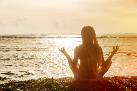Silhouette of beautiful woman with dreadlocks on his head, sitting near the ocean, meditating at sunset Stock Photo