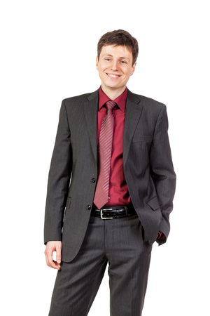 trouser: Portrait of young businessman in the business pose on isolated white background. Hands in trouser pockets Stock Photo
