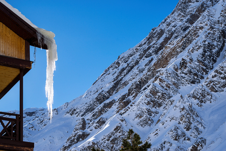 Corner of country house with long and dangerous icicles hanging on roof in winter on background of beautiful scenery in mountains