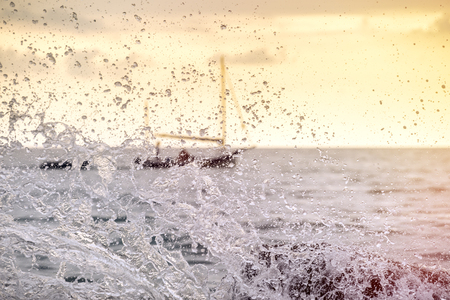 Splashes at sea from strong wave and of a sailing ship floating on a blurred background 스톡 콘텐츠