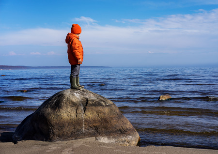 Little boy standing on shore of lake on large stone and looks into distance in the sunny day