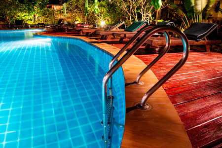 Swimming pool with wooden deck and stair. Romantic evening lighting setting near the pool, has landscaped gardens with tropical flora and plenty of comfortable sunbeds Фото со стока