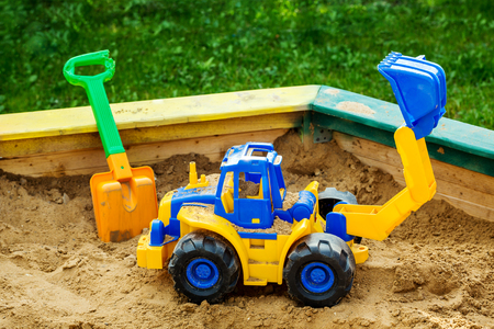 Children's toy tractor in sandbox close up