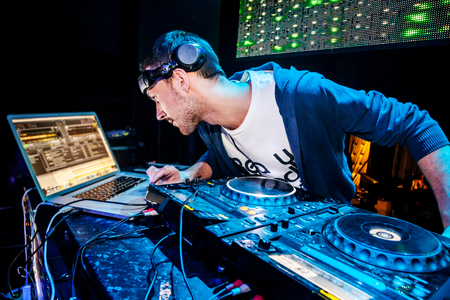 DJ with headphones looking in the laptop and mixes the track in nightclub at party