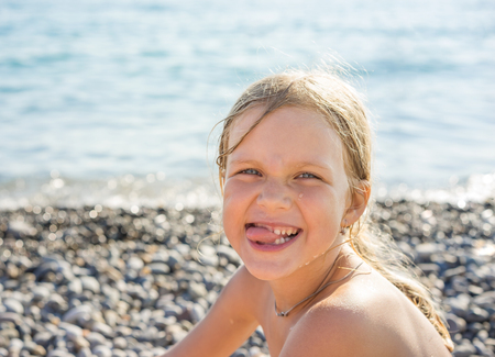Portrait of young beautiful blonde girl with blue eyes with a smiling and positive expression of the face, sitting on beach near the sea on background