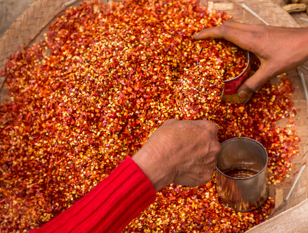 Red Chili pepper powder with seeds. Womans hands in motion are filled into jars pepper