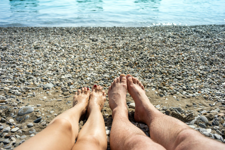 Womens and mens feet on the sea pebbles. Young happy couple sunbathing on the beach near the water Stock Photo