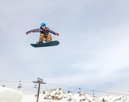 Jumping snowboarder in mountains on the snowboard Banque d'images