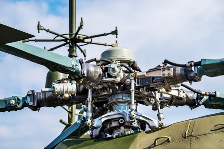 Military helicopter rotor blade detail closeup on background blue sky and clouds Фото со стока