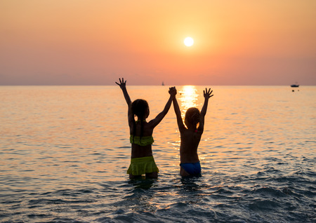 Silhouette of two happy little young girls jumping in sea at sunset