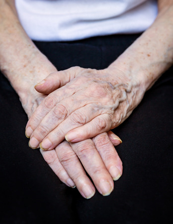 Close up of elderly female hands on black background