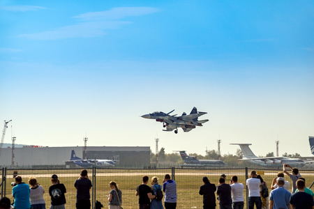 ZHUKOVSKY, MOSCOW - AUG 26, 2015: Spectators in the stands and Russian fighter aircraft MIG-29 at