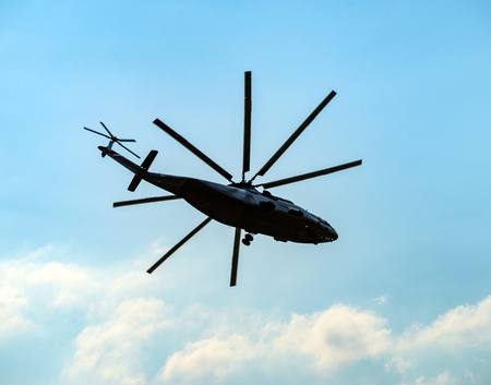 Silhouette of heavy transport helicopter flying against the blue sky
