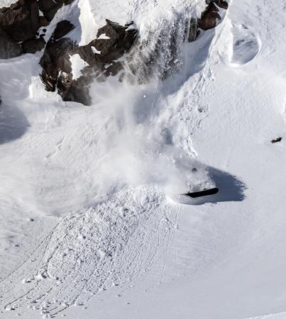 Freerider snowboarder jumping off a cliff Standard-Bild