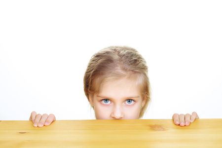 Portrait of young blonde girl with serious look from under table isolated on white background