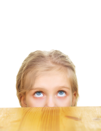 Portrait of young blonde girl looking up from under table isolated on white background