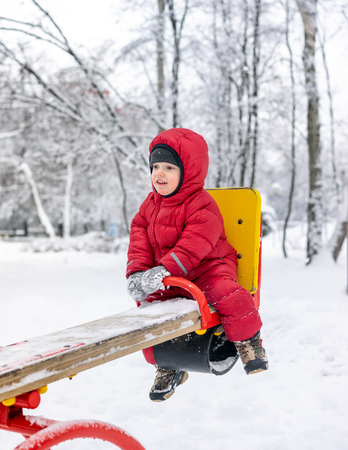 Little boy on the playground in winter day riding on a swing