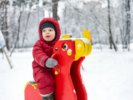 Portrait of a three year boy in winter clothes on a wooden horse in the city park in winter on the playground