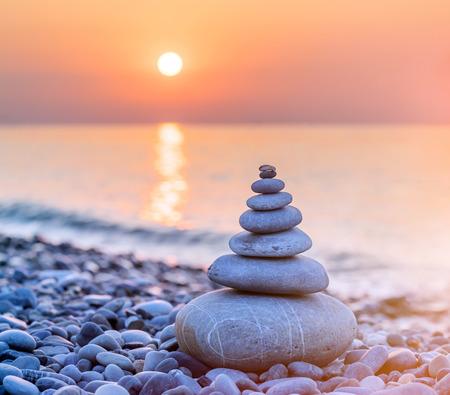 Pyramide von Steinen für die Meditation, die bei Sonnenuntergang an der Meeresküste liegt