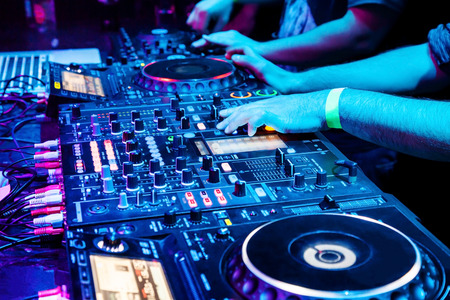 Dj mescola la traccia in discoteca alla festa. Parte del corpo sul pannello di controllo della musica del DJ