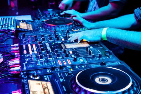 Dj mezcla la pista en discoteca en fiesta. Parte del cuerpo en el panel de control de música del DJ