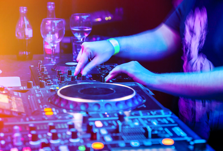 Dj mixes the track in nightclub at party. Body part on the DJ's music control panel Stock Photo