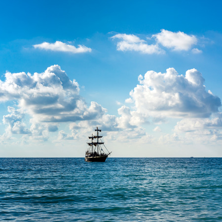 Historic old sailing ship in the sea on the background blue sky and clouds