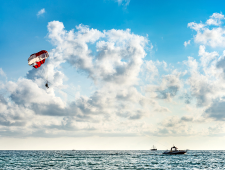 Silhouette of people on a parachute flying behind a motorboat on a holiday by the sea against the blue sky with clouds 스톡 콘텐츠