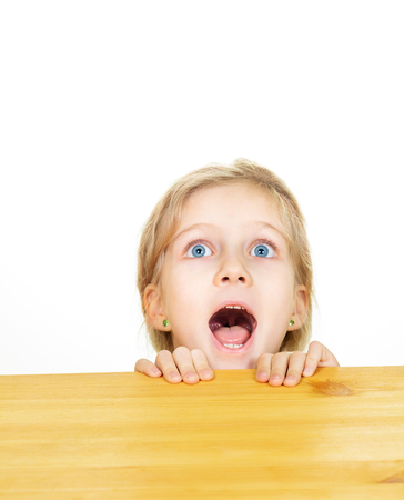 Portrait of young blonde girl looking up emotionally with open mouth from under table isolated on white background